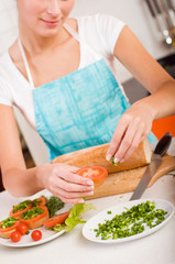 Attractive smiling woman preparing fresh healthy sandwiches in h