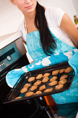Beautiful brunette woman in the kitchen baking cookies. (shallow