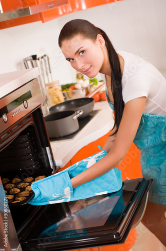 Beautiful brunette woman in the kitchen baking cookies.