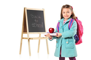 A child next to a school board holding books and red apple
