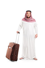 Full length portrait of an Arab tourist carrying a suitcase