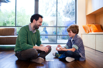 Father and son playing cards on wooden floor