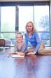 Grandmother and granddaughter on wooden floor with sketchbook