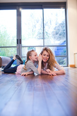 Mother and daughter laying on wooden floor whispering