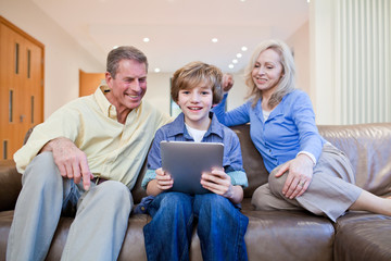 Grandparents on couch watching grandson using digital tablet