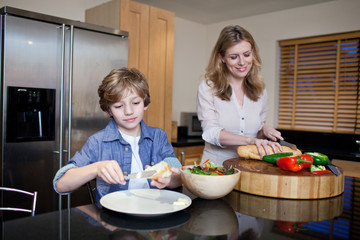 Mother and son preparing healthy meal in kitchen