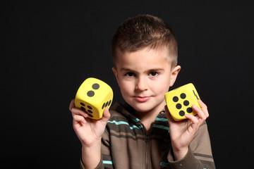 bambino mostra dadi gialli