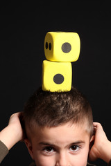 bambino con dadi gialli sulla testa
