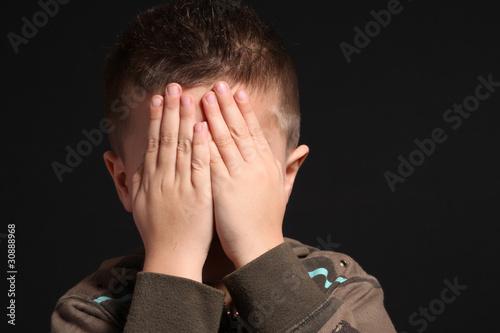 bambino si copre il volto con le mani