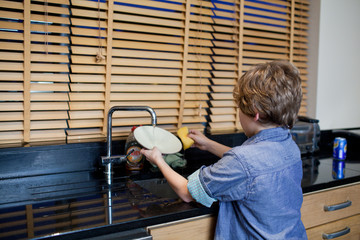 Boy doing the dishes in kitchen