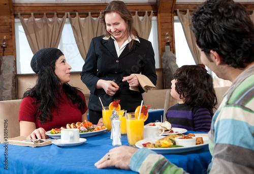 Szczęśliwa rodzina o śniadanie w restauracji