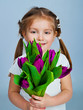 Cute little girl giving tulips
