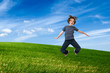 Child jumping on green field