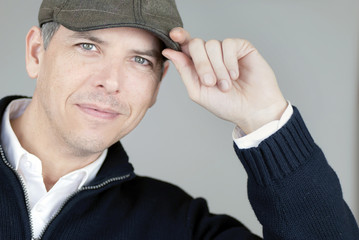 Smiling Confident Man Tips Newsboy Hat To Camera