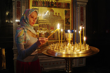 The Christian girl in an orthodox temple about burning candles