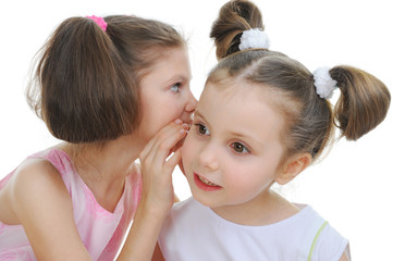 Two beautiful girls telling secret
