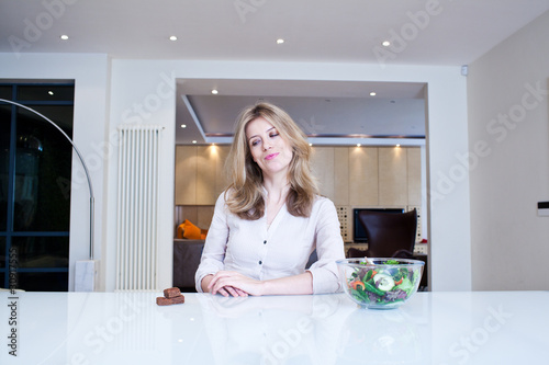 Indecisive woman sitting at table with chocolate and salad