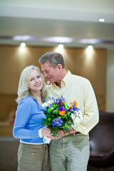 Smiling couple holding bunch of flowers