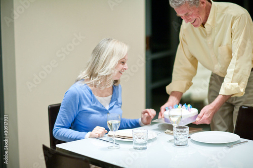 Man serving birthday cake to wife in dining room