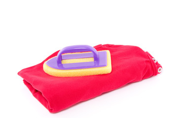 a plastic flat-iron on top of laundry isolated over white