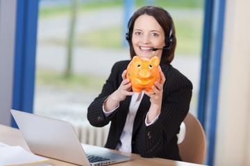 lächelnde frau mit sparschwein am arbeitsplatz