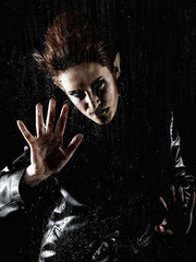 Portrait horrible fashion vampire woman behind rainy window