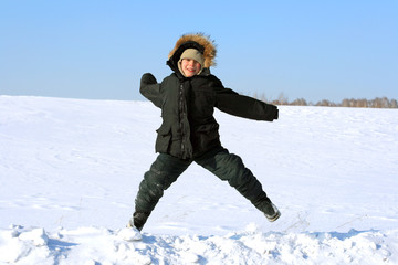 happy kid jumping in the winter field