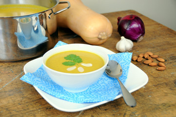 Squash soup in bolw with pot and ingredients