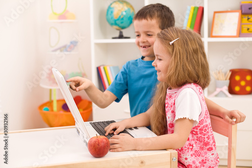 Kids playing on laptop computer at home