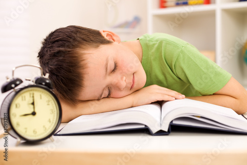 Boy fallen asleep on his book while studying