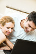 Young happy smiling couple working with laptop at home
