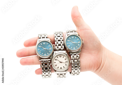 Three wristwatches on women`s hand isolated on white background