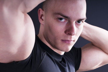 Portrait of sexy young man showing his muscular arms