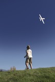 Boy stands on hilltop flying model plane