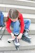 Mädchen zieht Rollschuhe an