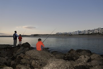 Father with two suns fishing on Paradise beach of Langebaan, South Africa