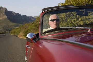 Senior man in vintage racing car on Signal Hill, Cape Town, South Africa