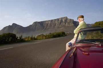 Senior man admires view leaning on vintage racing car on Signal Hill, Cape Town, South Africa