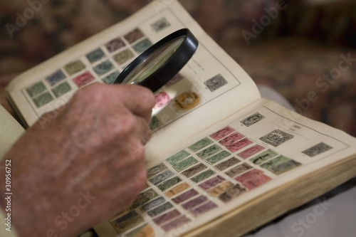 Senior man looks at stamp collection with magnifying glass