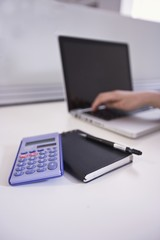 A notepad, calculator and laptop in an office