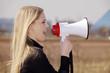 Blonde junge Frau mit Megafon auf freiem Land ruft