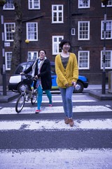 Two female adults walking across the zebra crossing