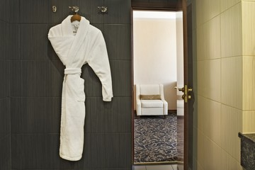 Interior of a hotel room with a white dressing gown hanging up and the door open with a view through to the next room