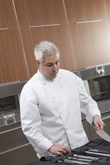 Mid- adult chef chooses knife