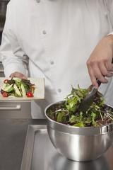 Mid- adult chef prepares leaf vegetables