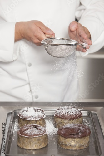 Mid- adult chef sieves icing sugar over chocolate cakes