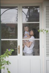 Mother and toddler standing inside a door with glass windows