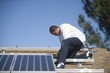 A man on a rooftop working on solar panelling