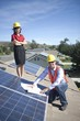 Two business people on a rooftop next to solar panelling with a set of plans