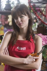 Florist stands holding scissors with arms folded